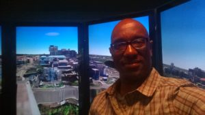 Coates in front of the liquid galaxy, a panoramic view of the earth based off the Earth code.  It's so large visitors actually feel immersed in the scene.