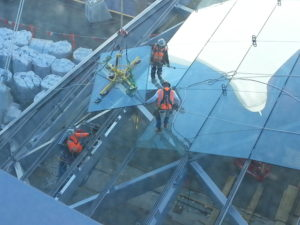 Robertson helps design train stations and makes sure they're dry and safe for Denver's commuters. Construction workers placing glass on a steel frame.
