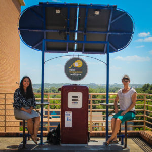 Karen Magid, Huston-Tillotson's Director of Sustainability, and Romero sitting at the solar-powered charging station on campus. (Austin, TX)